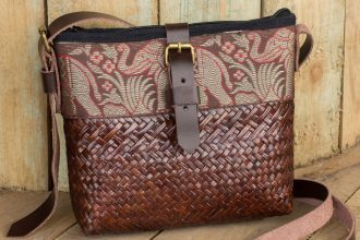 Hand Woven Sedge Shoulder Bag with Leather Accents, 'Thai Elephant Parade on Brown'